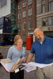 Man and woman looking at drawings or diagrams, standing in front of a building, smiling.
