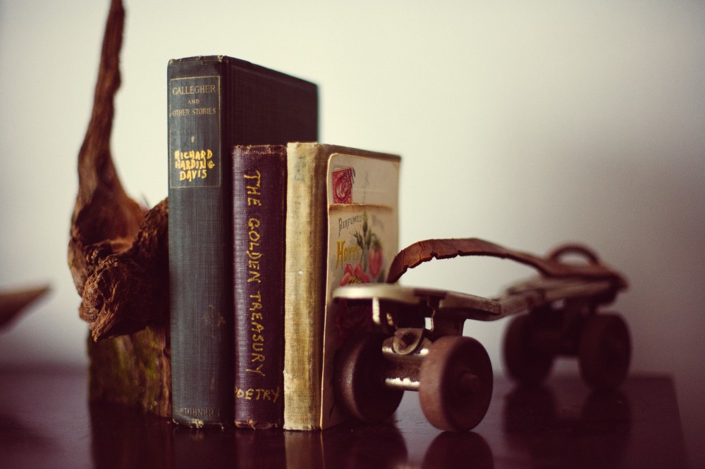 A display of three books propped by a piece of wood and a roller skate on either side. Intangible indexing terms could include e.g. leisure, memento, roller skates and display.